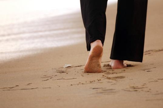 Frau geht entlang des Strandes